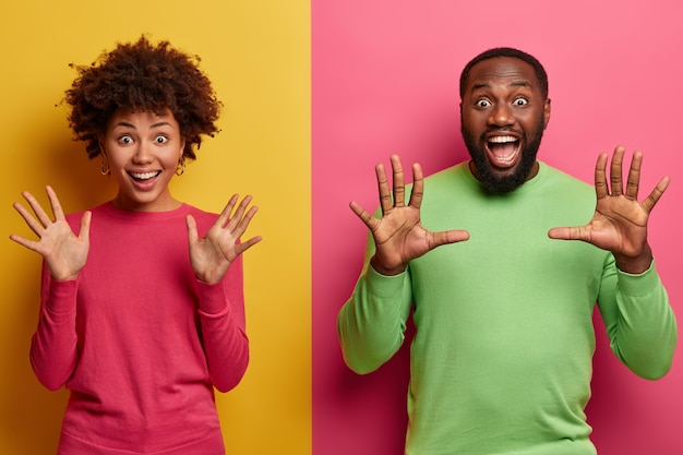 Tiro al coperto di donna e uomo etnici ipermotivi felicissimi alzano i palmi, fissano emotivamente, lieti di vedere sorprendente sorpresa, bocche aperte