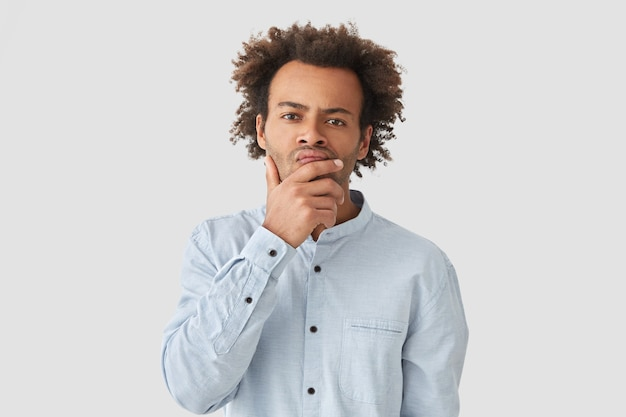 Indoor shot of pensive african american guy holds chin and looks with serious expression, thinks over his problem, wears elegant-shirt, has afro curly hairstyle, isolated