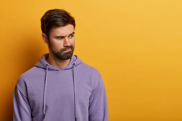Indoor shot of pensive bearded man concentrated aside, has sullen expression, thinks deeply about something, wears casual sweatshirt, poses over yellow wall, copy space for advertisement