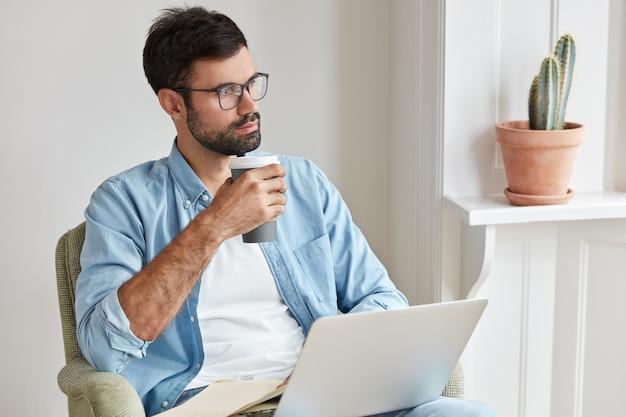 Indoor shot of pensive skilled freelancer working at home