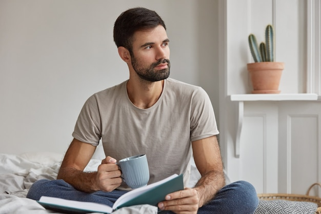 Indoor shot of pensive young caucasian guy with thick beard, being deep in thoughts, holds book and cup of tea, poses on bed