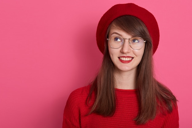 Indoor shot of pensive young female dresses red sweater, beret and round spectacles, looks thoughtfully aside as plans something interesting or insidious.