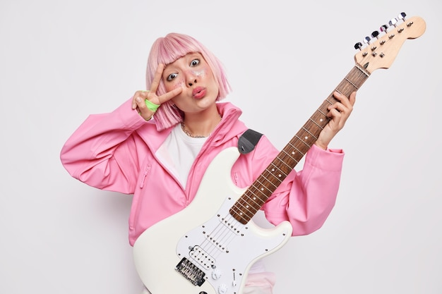 Indoor shot of pink haired woman rock n roll singer makes peace gesture over eye keeps lips folded poses with acoustic guitar has rehearsal before concert