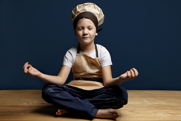 Indoor shot of playful handsome little boy sitting barefooted on floor in the kitchen, wearing chef hat and apron, keeping legs folded and eyes closed, doing meditation before baking cookies