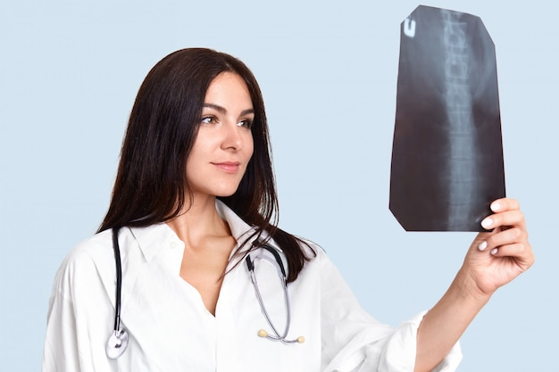 Indoor shot of pleasant looking female nurse or doctor looks attentively and happily at x ray