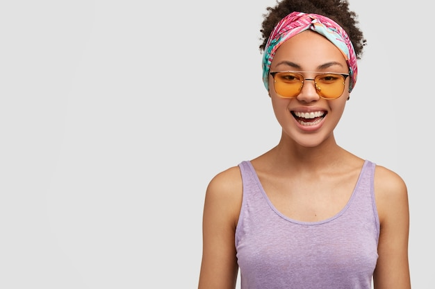 Indoor shot of pleasant looking happy african american woman chuckles positively