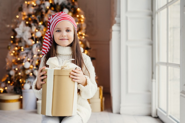 Indoor shot of pleasant looking small kid with blue charming eyes, wears santa hat, holds present in wrapped box