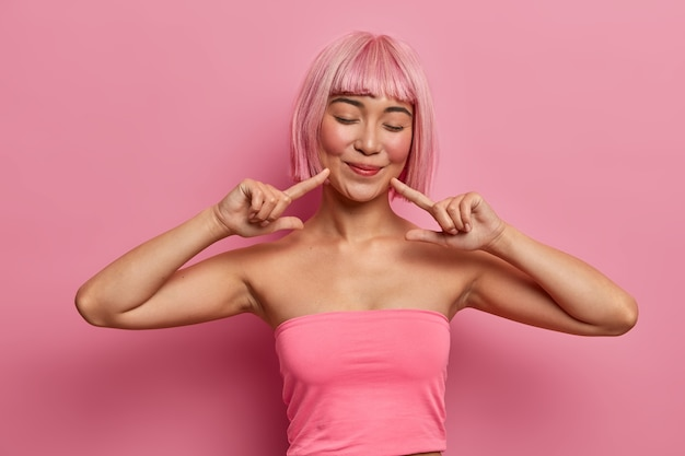 Tiro al coperto di una giovane donna asiatica dall'aspetto piacevole chiude gli occhi, indica gli angoli della bocca, attira la tua attenzione sul suo sorriso sul viso, vestita con un top corto casual, ha un'acconciatura rosa alla moda