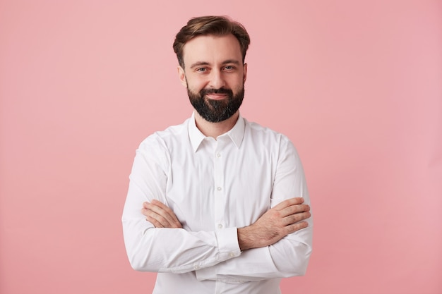 Indoor shot of pleasant looking young bearded brunette man with trendy hairstyle crossing hand on his chest while standing over pink wall, dressed in white shirt