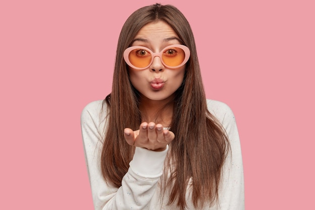 Indoor shot of pleasant looking young brunette caucasian woman in trendy sunglasses, makes air kiss on distance