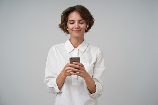 Indoor shot of pleasant looking young woman with short brown hair wearing white shirt while posing, keeping smartphone in her hands and typing message