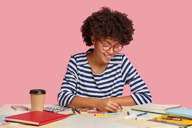 Indoor shot of pleased artist holds crayon