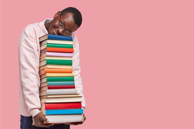 Indoor shot of pleased dark skinned man leans at pile of books, dressed in casual sweater, wears round spectacles