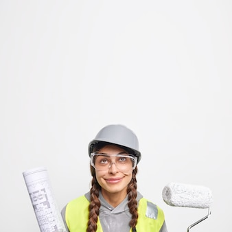 Indoor shot of pleased woman engineer holds painting roller and paper blueprint looks above works on construction site