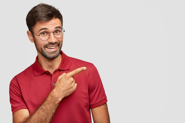 Indoor shot of positive bearded male in casual red t-shirt, points with index finger aside