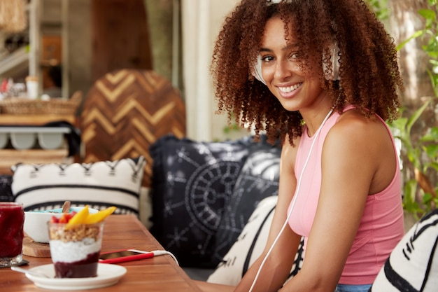 Indoor shot of positive female with bushy hairstyle, uses mobile application, enjoys favourite song, sits in cozy restaurant, eats tasty dessert. african american woman listens music in headphones