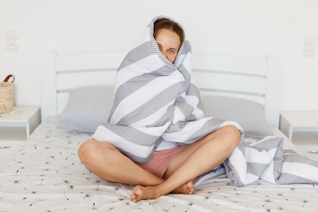 Indoor shot of positive female wrapped , sitting on bed in light bedroom wrapped in gray and white striped sheet, having shy expression, peeping from blanket.