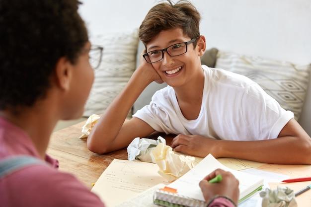 Tiro al coperto di compagni di classe amichevoli positivi lavorano insieme: ragazza intelligente e irriconoscibile aiuta il ragazzo asiatico con la preparazione all'esame