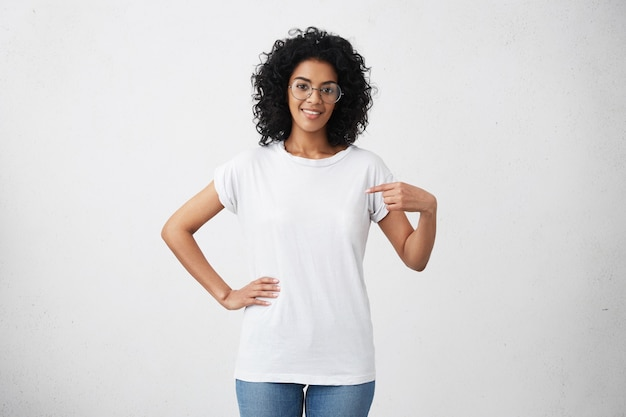 Indoor shot of positive friendly young mixed race female in glasses pointing