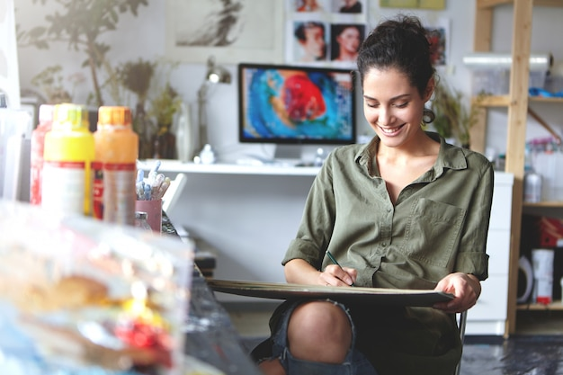 Indoor shot of positive happy young caucasian female artist smiling broadly while working on painting or sketches at workshop; painting stuff