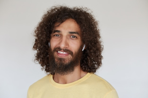 Indoor shot of positive lovely young bearded male with brown curly hair looking cheerfully with wide smile, wearing yellow t-shirt