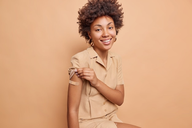 Indoor shot of positive woman with curly hair shows vaccinated arm with plaster gets second dose of vaccine happy to feel protected raises sleeve of dress isolated over beige wall