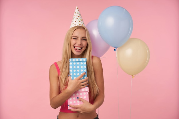 Indoor shot of positive young long haired female rejoicing while posing in multicolored air balloons, having fun on birthday party and holding gifts, standing over pink background