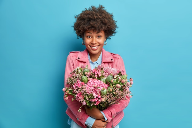 Indoor shot of positive young woman embraces big bunch of flowers smiles pleasantly dressed in pink jacket isolated over blue wall