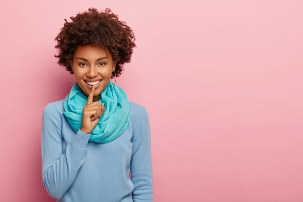 Tiro al coperto di una donna dalla pelle piuttosto scura chiede di tacere, fa un gesto di silenzio, indossa un maglione blu e una sciarpa sul muro roseo