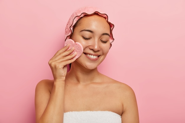 Indoor shot of pretty young asian female uses cosmetic sponge for makeup removal, has problematic fat skin, focused down with tender smile, wrapped in towel isolated on pink wall. beauty concept