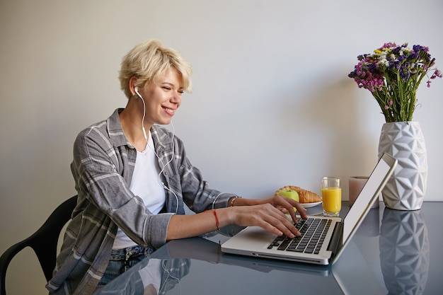 Indoor shot of pretty young female with short blond hair sitting at table with laptop, drinking orange juice, chatting with friend, posing over home interior