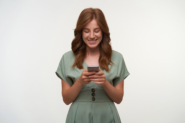 Indoor shot of pretty young lady in romantic dress holding smartphone in her hands, looking at screen and smiling cheerfully, isolated