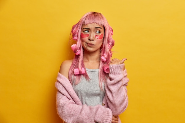 Indoor shot of puzzled asian girl has long pink hair, makes curly hairstyle with curlers, points away on copy space, has displeased expression