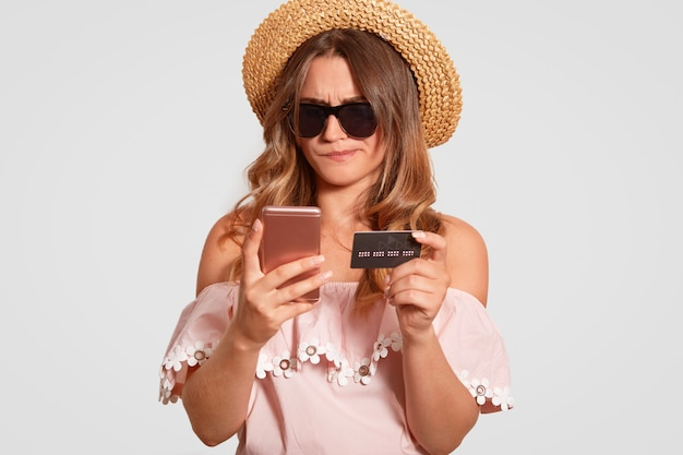 Indoor shot of puzzled indignant woman traveller checks her bank account, holds modern cell phone and plastic card