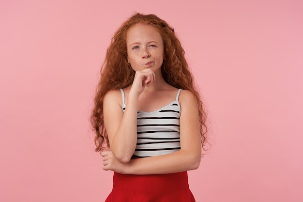 Indoor shot of redhead curly female kid with casual hairstyle wearing red skirt and striped top, holding her chin with raised hand and looking at camera thoughtully, isolated over pink background