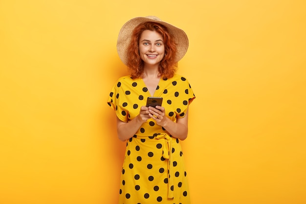 Tiro al coperto di donna rossa in posa in abito giallo a pois e cappello di paglia