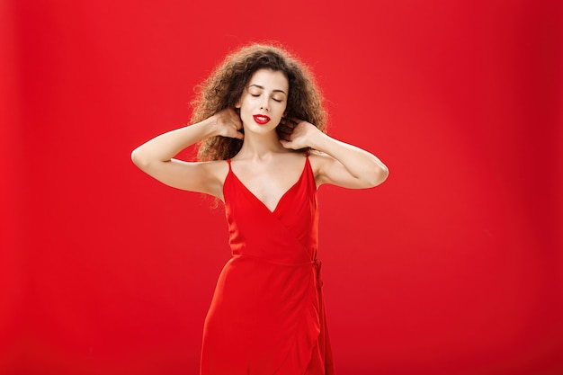 Indoor shot of relaxed woman messaging back of neck with closed eyes and calm carefree expression standing in elegant evening dress with curly hairstyle against red background pleased and tired.