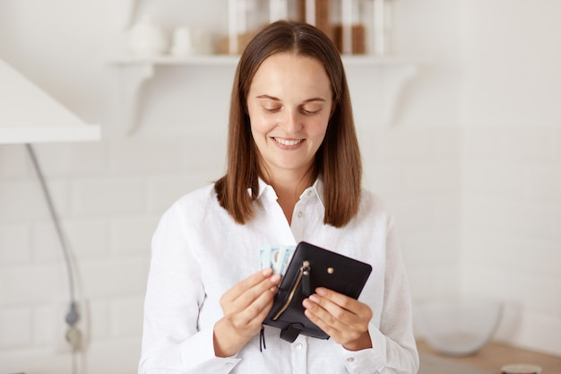 Indoor shot of rich woman wearing white casual style shirt, posing in light kitchen with black wallet in hands, counting her savings before going shopping.
