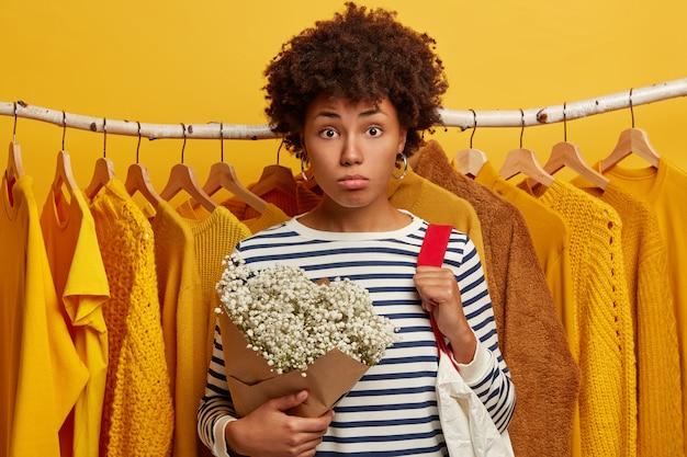 Indoor shot of sad curly woman wears striped sailor jumper, holds bouquet, carries bag on shoulder