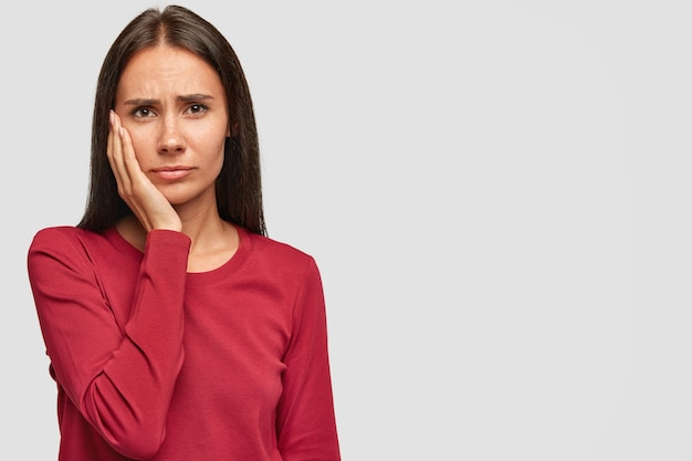 Indoor shot of sad unhappy european woman with unhappy expression, keeps palm on cheek, wears casual red sweatshirt,