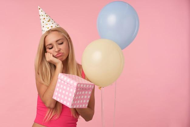 Tiro al coperto di triste giovane donna bionda in abito da vacanza mantenendo la confezione regalo, tenendo il mento sulla mano sollevata e guardando la scatola con disappunto, in piedi su sfondo rosa e palloncini di elio