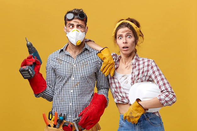 Indoor shot of scared woman wearing protective gloves holding hardhat leaning at her husband's shoulder who is going to fix shelves in room. untidy handyman and his cute wife
