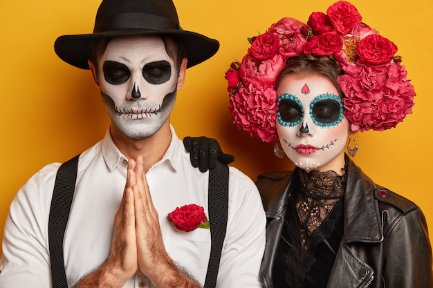 Indoor shot of scary couple with skull makeup, wear traditional mexican attire, visit day of dead carnival, have spooky faces, man stands in praying pose