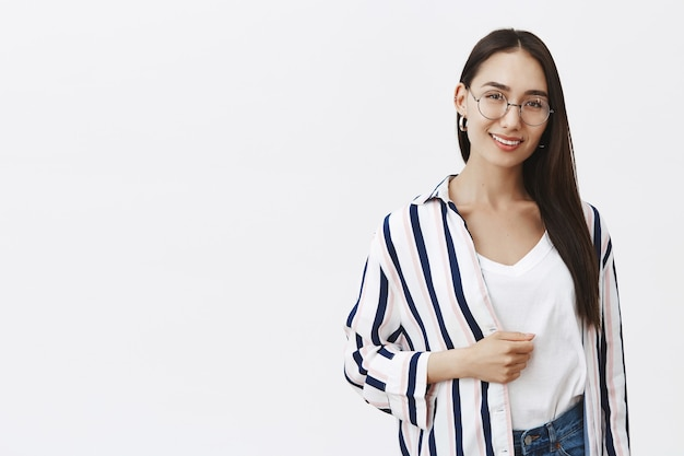 Indoor shot of self-assured feminine fashion model with long beautiful hair and natural beauty, standing in trendy striped shirt and smiling broadly