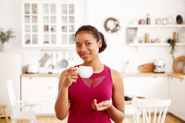 Indoor shot of self confident beautiful joyful young black dark skinned woman in stylish top having morning routine before run in park, holding white mug, enjoying fresh coffee
