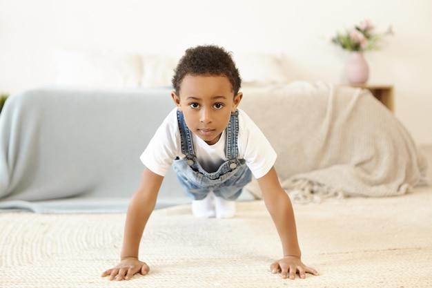 Indoor shot of self determined disciplined african american black schoolboy exercising