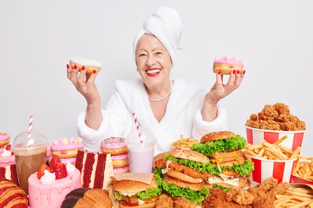 Indoor shot of senior woman smiles broadly and holds two delicious doughnuts has happy mood eats junk food