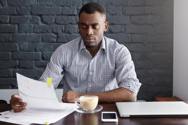Tiro al coperto di serio finanziere afro-americano che studia documenti finanziari durante la pausa caffè al bar