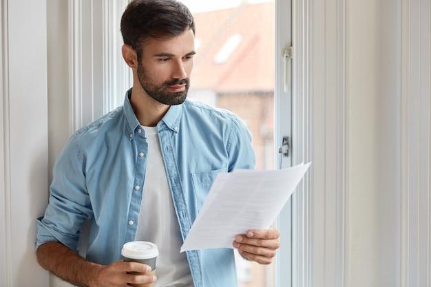 Tiro al coperto di freelance barbuto serio che lavora a casa