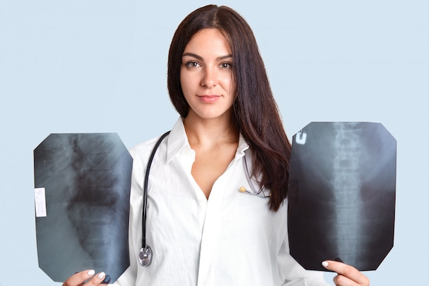Indoor shot of serious brunette female doctor with two x rays films, examines human`s spine, wears white robe with stethoscope, stands in patient`s room, isolated on light blue.